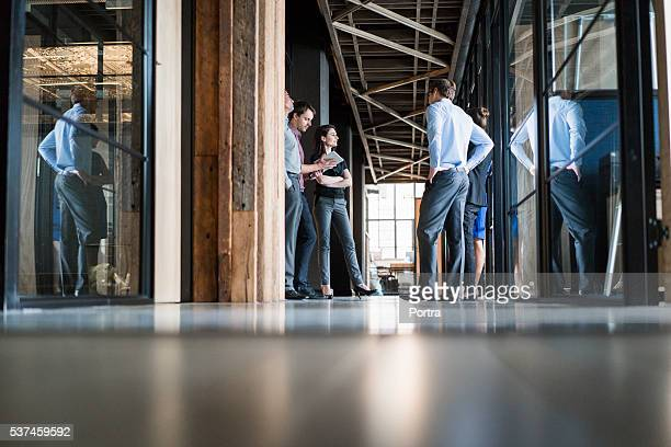 Business people discussing in office corridor