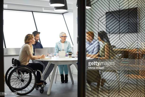 business people discussing in office meeting - disabilitycollection stock-fotos und bilder