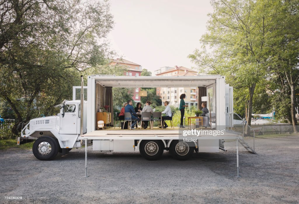 Business People Discussing In Portable Office Truck At Park High-res Stock Photo