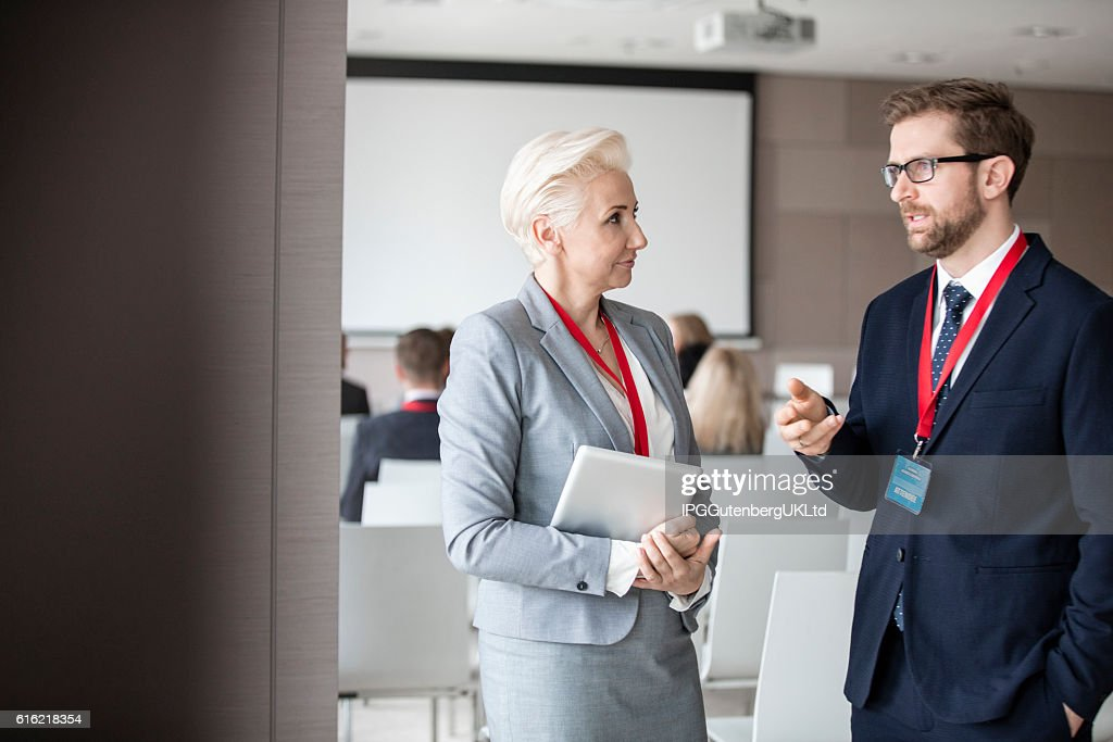 Business people discussing in seminar hall : Stockfoto