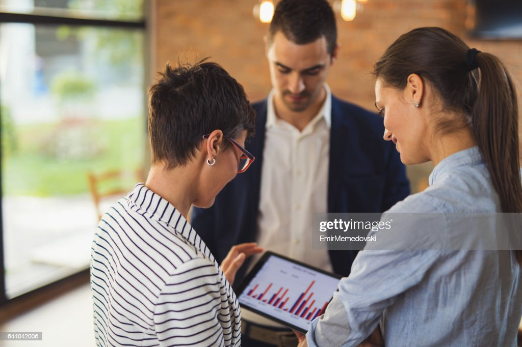 Business people discussing market research statistics during business meeting : Stock Photo