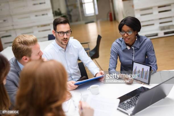 営業会議中に市場調査統計を論議しているビジネス人々。