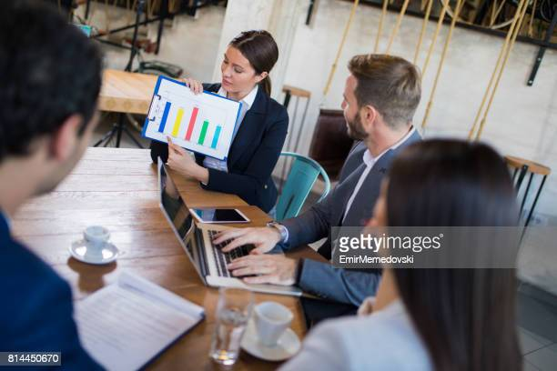 Business people discussing market research statistics during business meeting