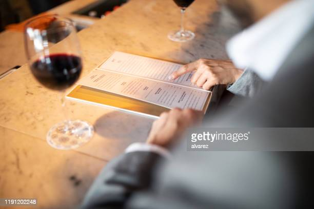business people discussing menu at a cafe counter - menu stock pictures, royalty-free photos & images