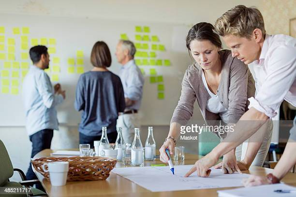 Business people discussing over blueprint at conference table