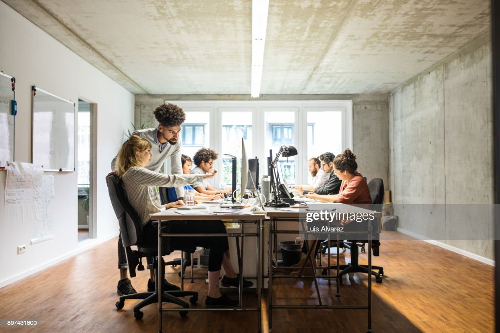 Business people discussing over computer in creative office : Stock Photo
