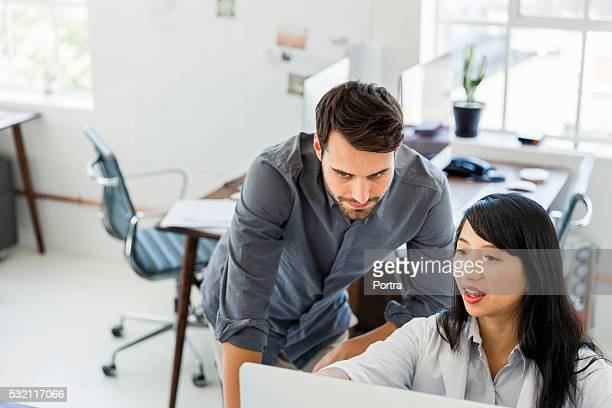 Business people discussing over computer in office