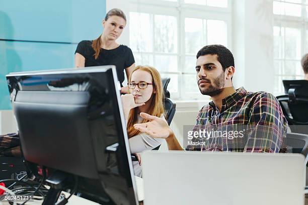 Business people discussing over desktop PC in creative office