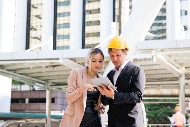Business People Discussing Over Digital Tablet While Standing Against Buildings