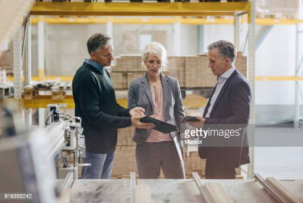 Business people discussing over digital tablet while standing at lumber industry
