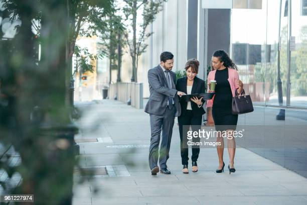 Business people discussing over documents while walking on footpath