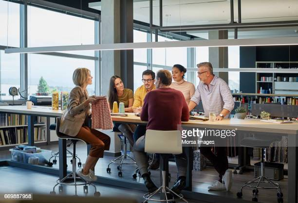 Business people discussing over fabric at table