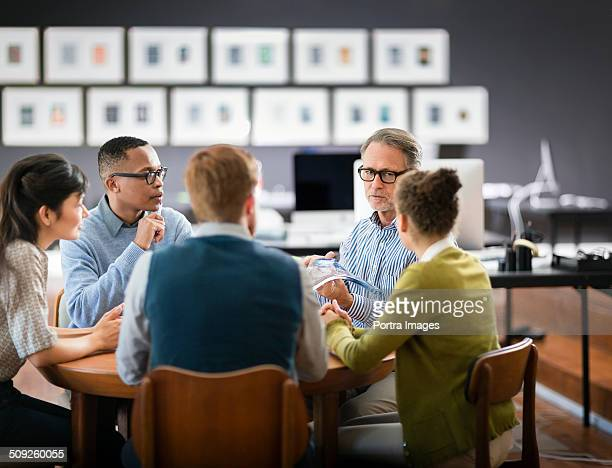 Business people discussing over glass model