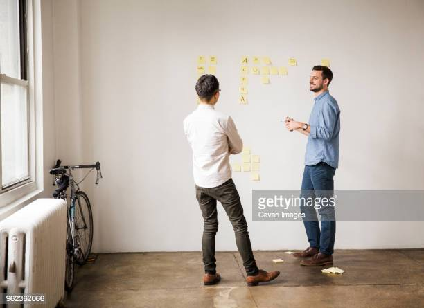Business people discussing over sticky notes against white wall at creative office
