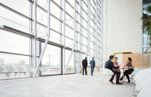 Business people discussing plans in modern lobby - gettyimageskorea