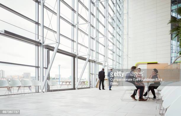 business people discussing plans in modern lobby - hotel lobby stock pictures, royalty-free photos & images