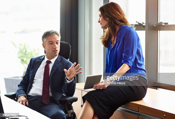 business people discussing project on ipad - older women in short skirts stock pictures, royalty-free photos & images