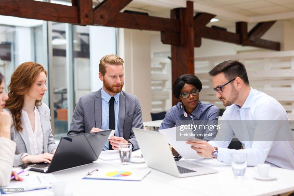 Hombres de negocios discutiendo la estrategia con un analista financiero : Foto de stock