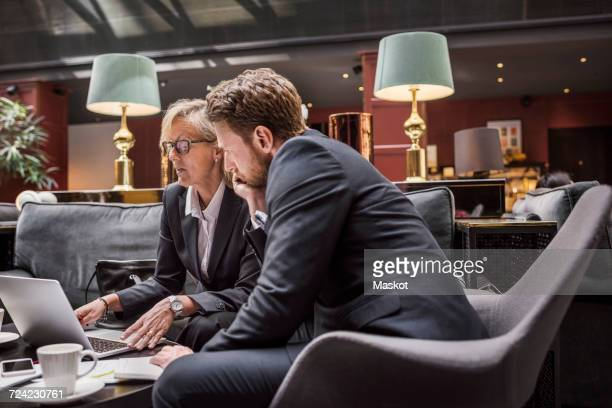 Business people discussing while looking at laptop in hotel reception