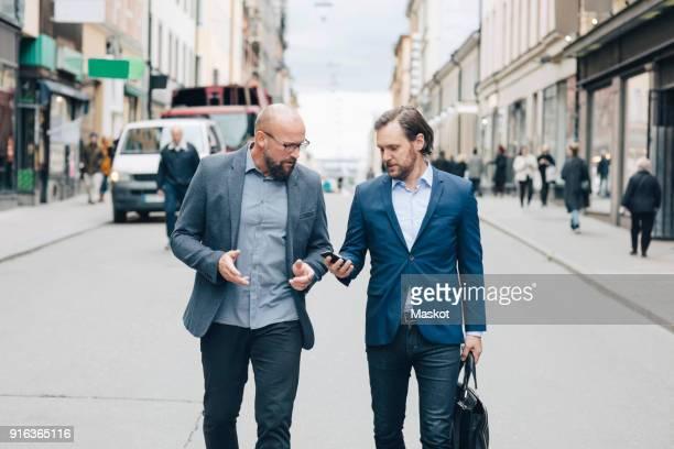 business people discussing while walking on street in city - nur erwachsene stock-fotos und bilder