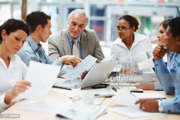 Pessoas de negócios a discutir o trabalho no computador portátil em uma reunião