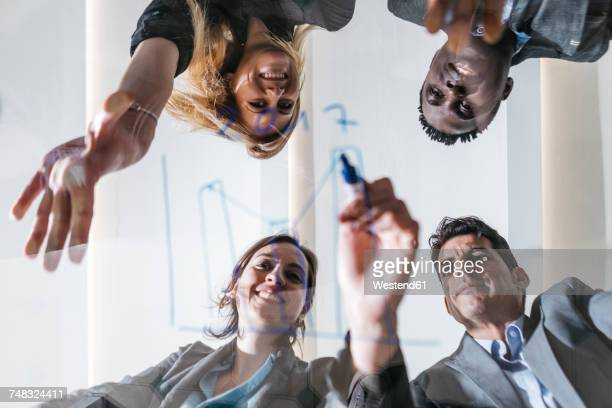 Business people drawing chart on glass screen