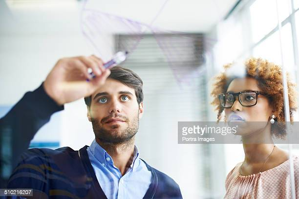 Business people drawing pie chart on glass wall
