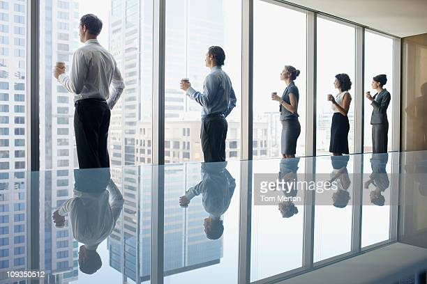 Business people drinking coffee and looking out window in conference room