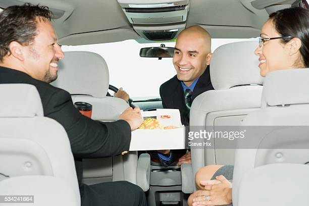 Business People Eating Donuts While Commuting