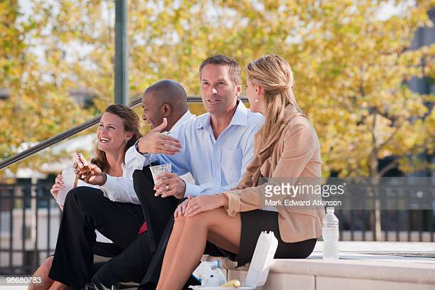 Business people eating lunch on steps