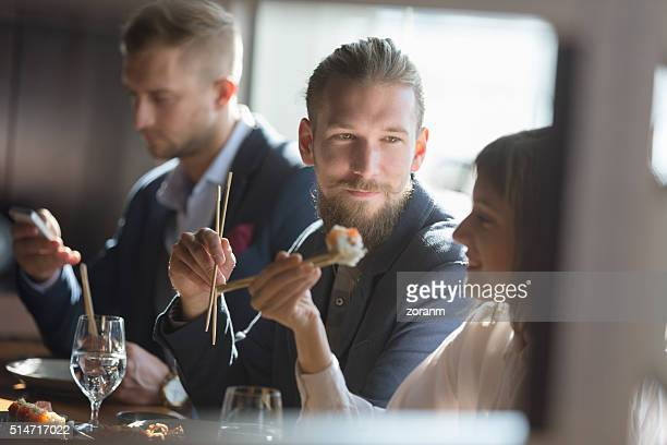 Business people eating sushi