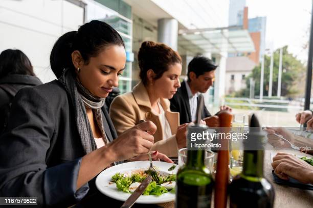 business people eating their lunch at a restaurant - hispanolistic stock photos and pictures