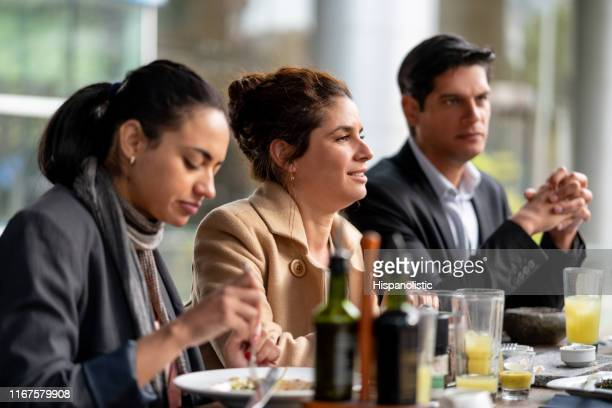 business people enjoying their lunch at a restaurant - hispanolistic stock photos and pictures