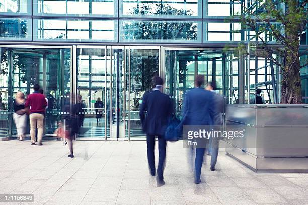 business people entering and leaving office building, motion blur - entrance stock pictures, royalty-free photos & images