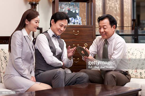 Business people examining antique with magnifying glass
