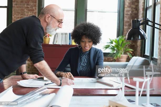 Business people examining blueprints on desk