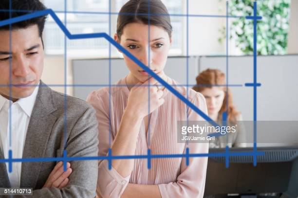 Business people examining graph on window