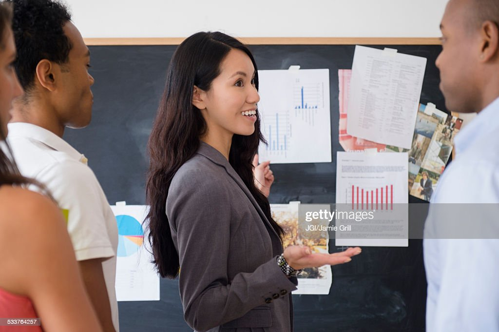 Business people examining presentation in meeting : Stock Photo