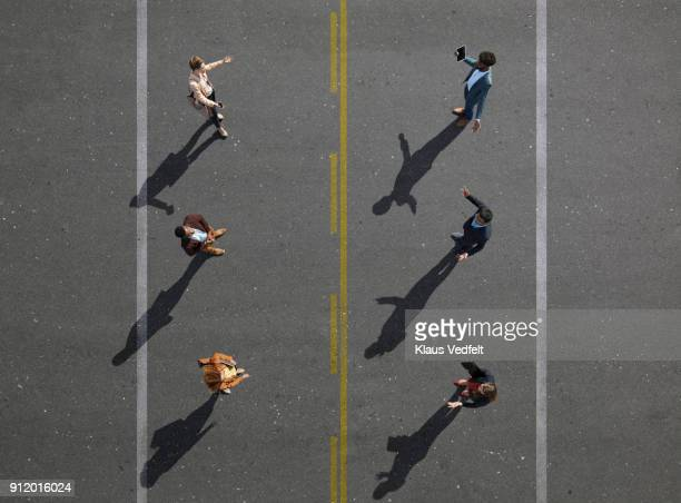 6 business people facing each other, standing on road painted asphalt