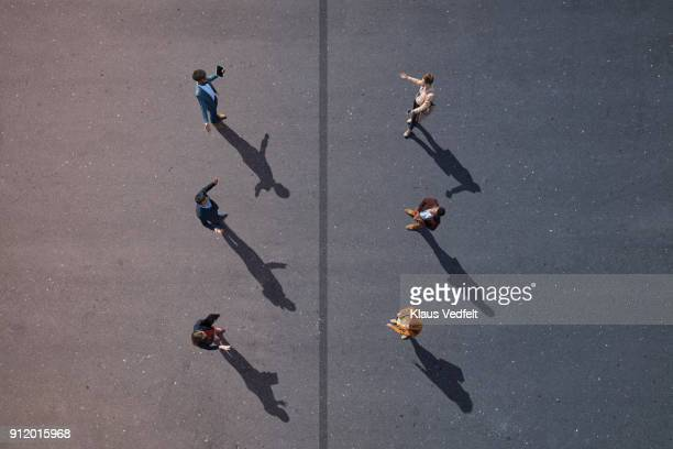 6 business people facing each other, with line dividing them, on painted asphalt - social distancing stock-fotos und bilder