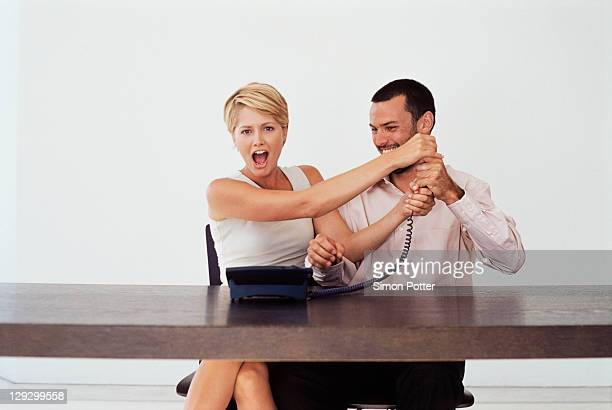 Business people fighting over telephone