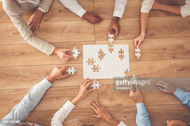 business people finding solution together at office - raadsel stockfoto's en -beelden