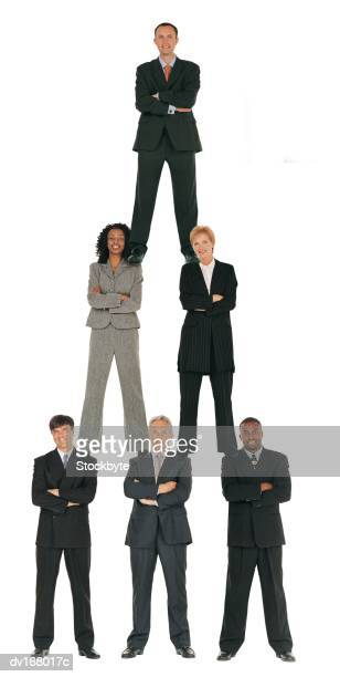 Business people forming human pyramid with businessman on top