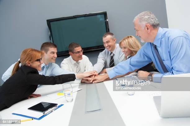 """Hommes et femmes d'affaires rassemblement mains à l'unité en hommage à l """" esprit d"""" équipe."""