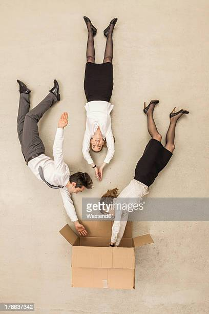 business people getting inside box - beige background stock pictures, royalty-free photos & images