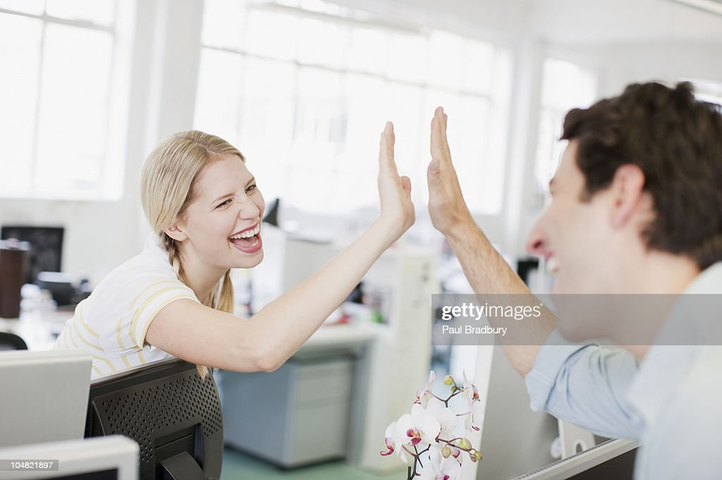 Business people giving high five in office : Stock Photo