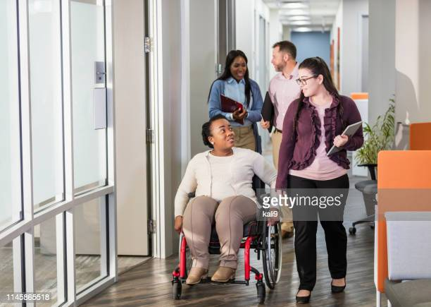 business people going to meeting, woman in wheelchair - differing abilities female business stock pictures, royalty-free photos & images