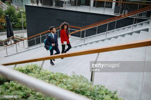 business people going up the stairs in downtown business district - finanza ed economia foto e immagini stock
