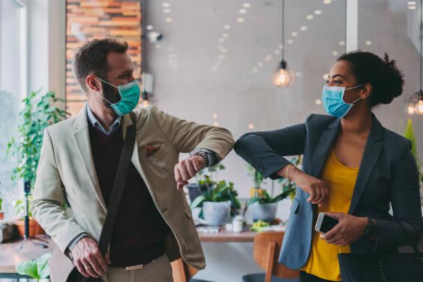 business people greeting during covid-19 pandemic, elbow bump - coronavirus foto e immagini stock
