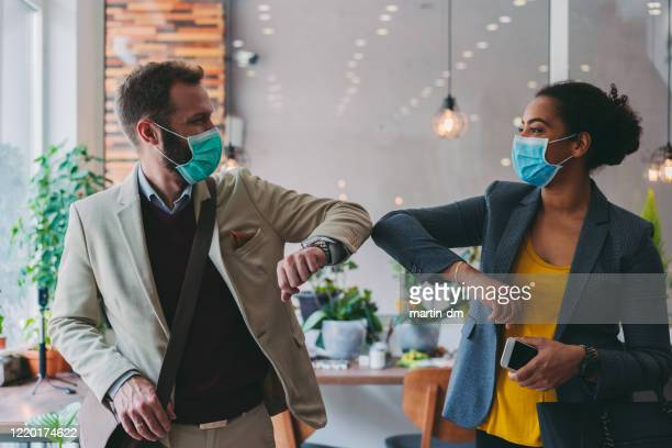 business people greeting during covid-19 pandemic, elbow bump - protective face mask stock pictures, royalty-free photos & images